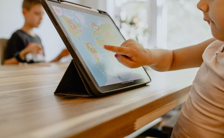 child on ipad looking at map
